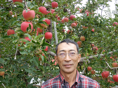 果樹園主 菊田透氏(背景は「陽光」10月6日撮影)