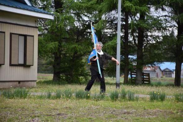 「さあ、今日も始めるぞ!」旗を担ぐ會田先生