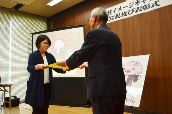 「しみちゃん」をデザインした高松絵美さん 松本村長より表彰状と盾が贈られました。