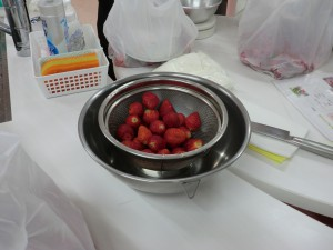 3~4人ずつの班で、収穫したいちごをジャムに加工しました。まずは、へたを取って洗います。