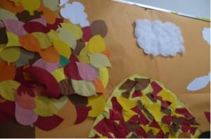 紅葉した山と木々が表現されました。色紙の配色は似ていますが、切り取った形が違うとやはり別々のものに見えて来ます。雲は綿を使用しています。